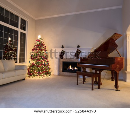 Bright Christmas tree in living room with burning fireplace and grand piano during night time.