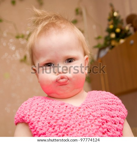 bright closeup portrait of adorable blond baby with blue eyes, with a grimace, and puffed-out cheeks - stock photo
