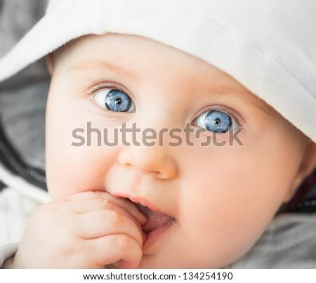 bright closeup portrait of baeutiful baby in the hood - stock photo
