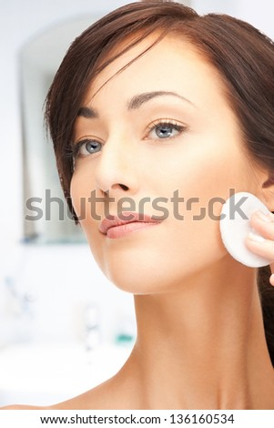 bright closeup portrait picture of beautiful woman with cotton pad - stock photo