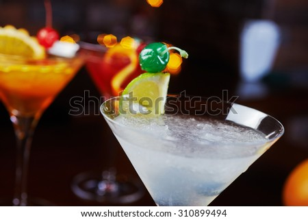 bright cocktail daiquiri with creative decoration of orange slices and ice on a wooden table in a bar or restaurant with a beautiful dance disco lights bokeh in the background. soft focus. - stock photo