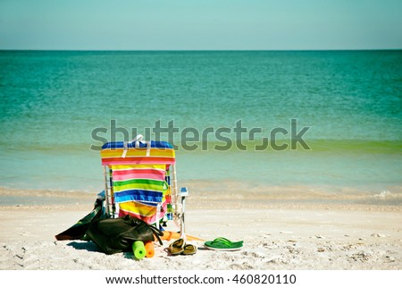 Bright Color Beach Chair with flip flops, floats and bag on the Beach