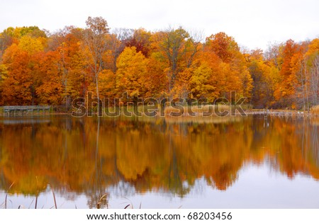 Bright colored autumn trees and reflections seen  in the lake - stock photo