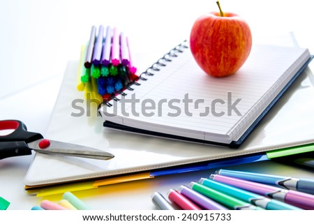 bright colored back to school supplies and an apple for the teacher
