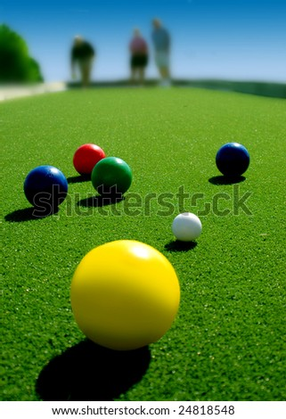 Bright colored Bocce balls on brilliant green court. Three players in background. - stock photo
