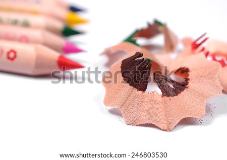 Bright colored pencils and color wood shavings on a white background - stock photo