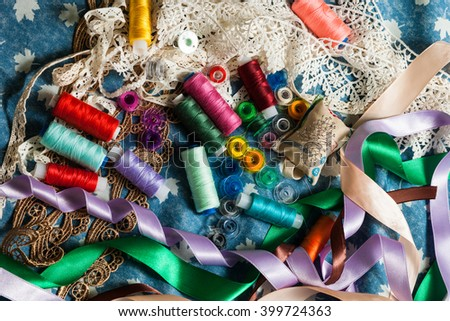 bright colored thread, bobbin, tape lace on blue denim background