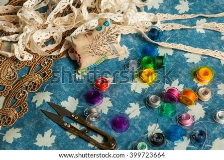 bright colored thread, scissors, pins, bobbin on a blue denim background - stock photo