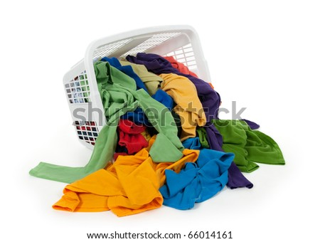 Bright colorful clothes falling out of a laundry basket. Isolated on white background. - stock photo