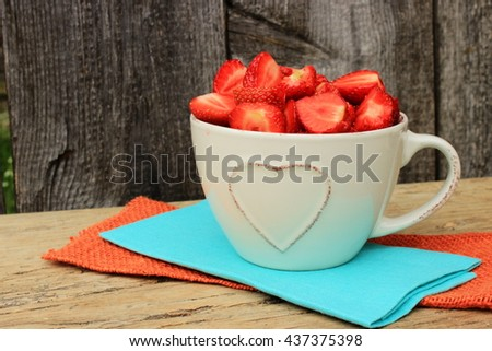 Bright colorful composition with large cup of sweet ripe strawberry on orange and turquoise linen napkins in a rustic setting. Healthy, natural food theme - stock photo