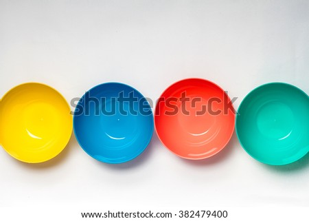 Bright colorful cup plastic disposable tableware on white background
