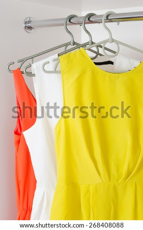 bright colorful  female dresses hanging on coat hanging  in white wardrobe - stock photo