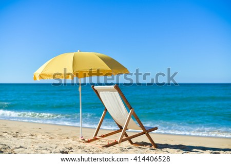 Bright colorful image of yellow umbrella and white wooden chair on Atlantic sandy beach blue sky copy space background - stock photo