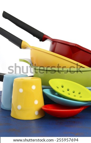 Bright colorful modern kitchen pot and pans in red, yellow, blue and green theme with spoons and salt and pepper shakers, on dark blue rustic wood table, vertical. - stock photo