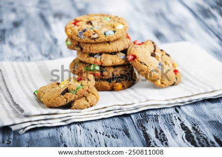 Bright, colorful oatmeal cookies on a napkin on a wooden background - stock photo