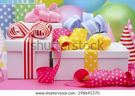 Bright colorful party table with balloons, streamers, party favor gift bags and gifts with bright color ribbons and bows.  - stock photo