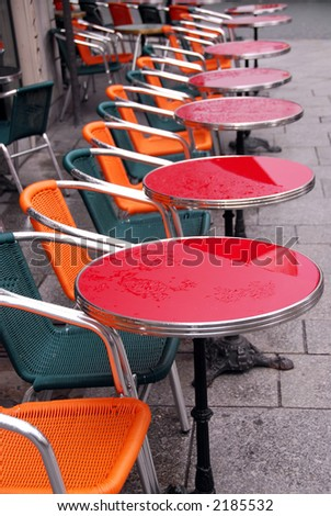 Bright colorful tables in a sidewalk cafe with rain drops - stock photo