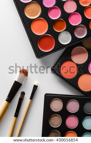 Bright colors for brave soultions in applying of make-up. Interesting blusher, lipstick and eyeshadow palettes are must have of every woman. Soft colors for blush. - stock photo