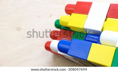 Bright colour building blocks on wooden surface. Concept of educational development tools. Slightly de-focused and close-up shot. Copy space.