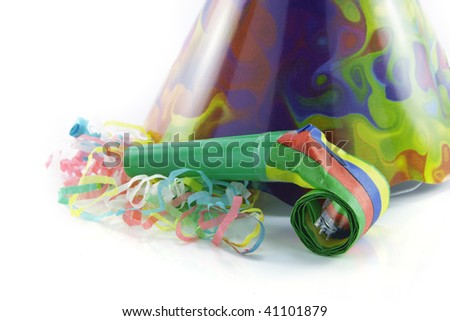 Bright cone shaped party hat and blower with party streamers on a reflective white background - stock photo