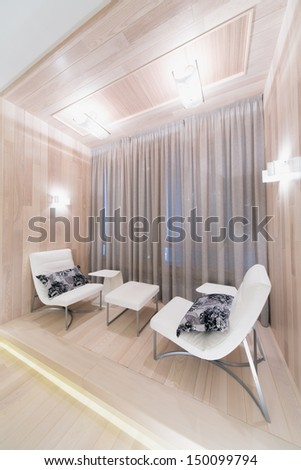 Bright contemporary lounge decorated tree with two chairs and a small table - stock photo