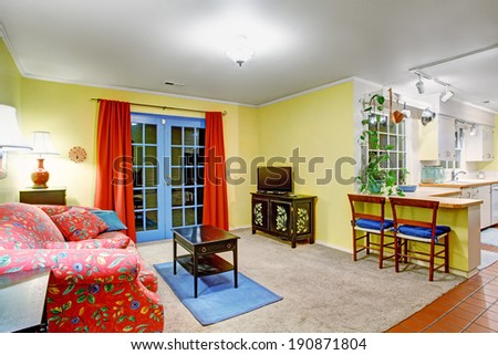 Bright contrast colors living room with red sofa, small black coffee table, blue french door with red curtains