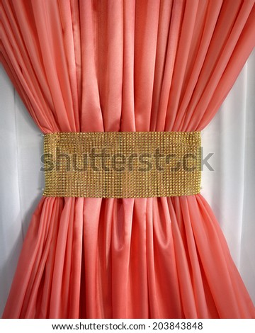 Bright coral crease fold curtain in the form of a bow gleaming light golden belt on white tulle background - stock photo