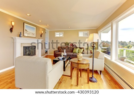 Bright cozy living room with beige walls, trimmed  fireplace and nice view