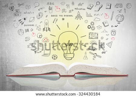 Bright creative idea light bulb over open textbook (shallow focus) with freehand doodle sketch drawing of educational knowledge and wisdom flowing on white grey cement concrete chalkboard background  - stock photo