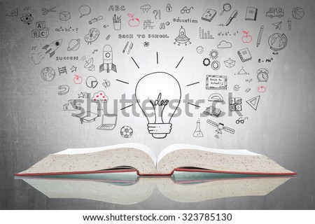 Bright creative idea light bulb over open textbook with freehand doodle sketch drawing of educational knowledge and wisdom flowing on white grey cement: Free thinkers  concrete chalkboard background   - stock photo