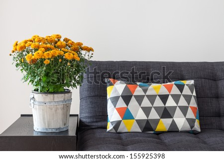 Bright cushion on a sofa, and orange chrysanthemums on a side table. - stock photo