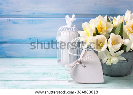 Bright daffodils and tulips  flowers in bucket, decorative heart and candle on turquoise  painted wooden planks against  blue wall. Selective focus.  - stock photo
