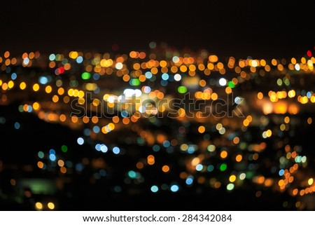 Bright defocused colored lights on black background - stock photo