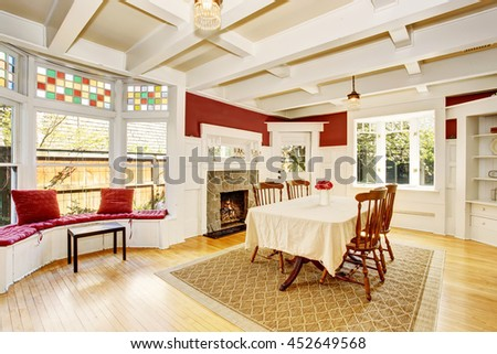 Bright dining room in red walls and white wooden trimmings. Also fireplace with stone decor and sitting area with wide window. - stock photo