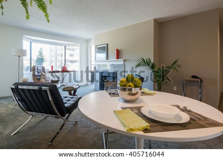 Bright dining room with a table set for dinner and a living room. Interior design. - stock photo