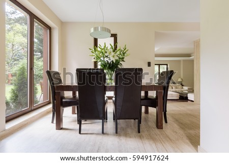 Bright dining space with wooden table, chairs and big window