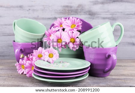 Bright dishes with flowers on wooden background - stock photo