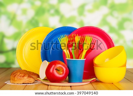 Bright disposable tableware, croissant and an apple on an abstract green background. - stock photo