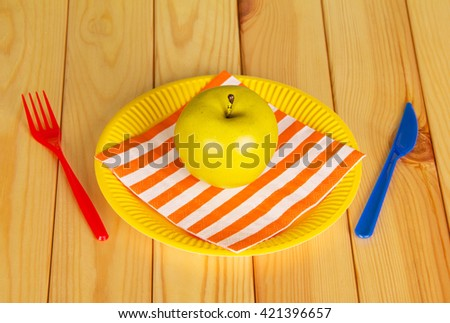 Bright disposable tableware, napkin and apple on a background of light wood. View from above.