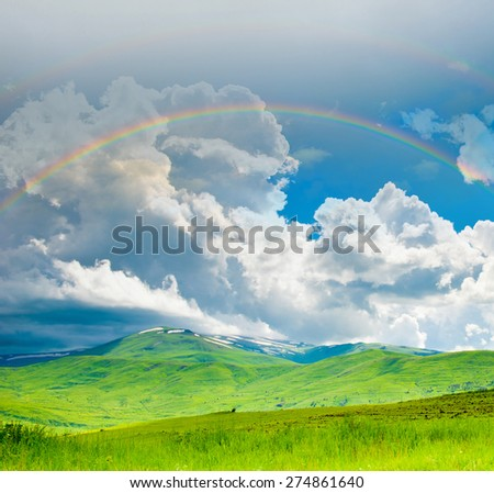 Bright double rainbow in the sky with clouds above the mountains in summer day - stock photo