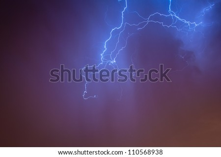Bright dramatic lightening stretched across the night sky over a cities ambient orange glow of lights giving it unique colors - stock photo