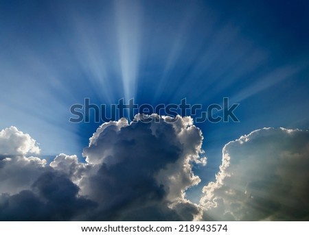 Bright dramatic sunlight through the clouds - stock photo