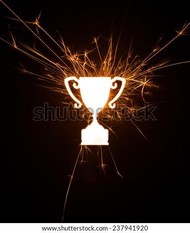 Bright dynamic sparkly trophy design set on black background with copy space. - stock photo