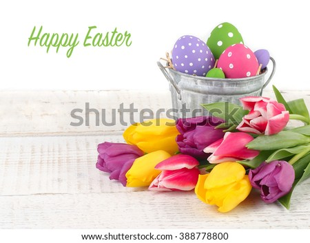 Bright Easter eggs in a bucket and spring tulips on a wooden background. An easter background with space for the text.