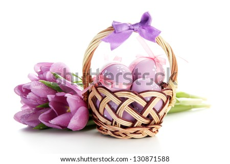 Bright easter eggs in basket and tulips, isolated on white - stock photo