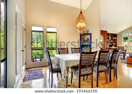 Bright elegant dining room with high ceiling and black table set