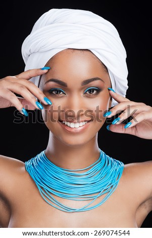 Bright emphasis. Beautiful African woman wearing white headscarf and smiling while looking at camera and standing against black background - stock photo