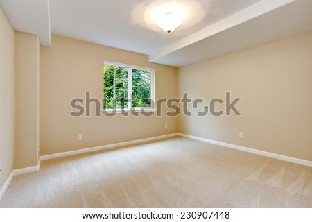 Bright empty bedroom in light ivory tone with carpet floor and small window - stock photo