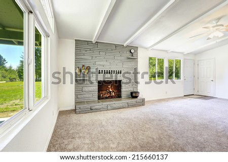 Bright empty living room with fireplace and carpet floor. Old house interior