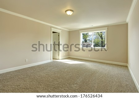 Bright empty room with one window, beige carpet floor and ivory walls - stock photo